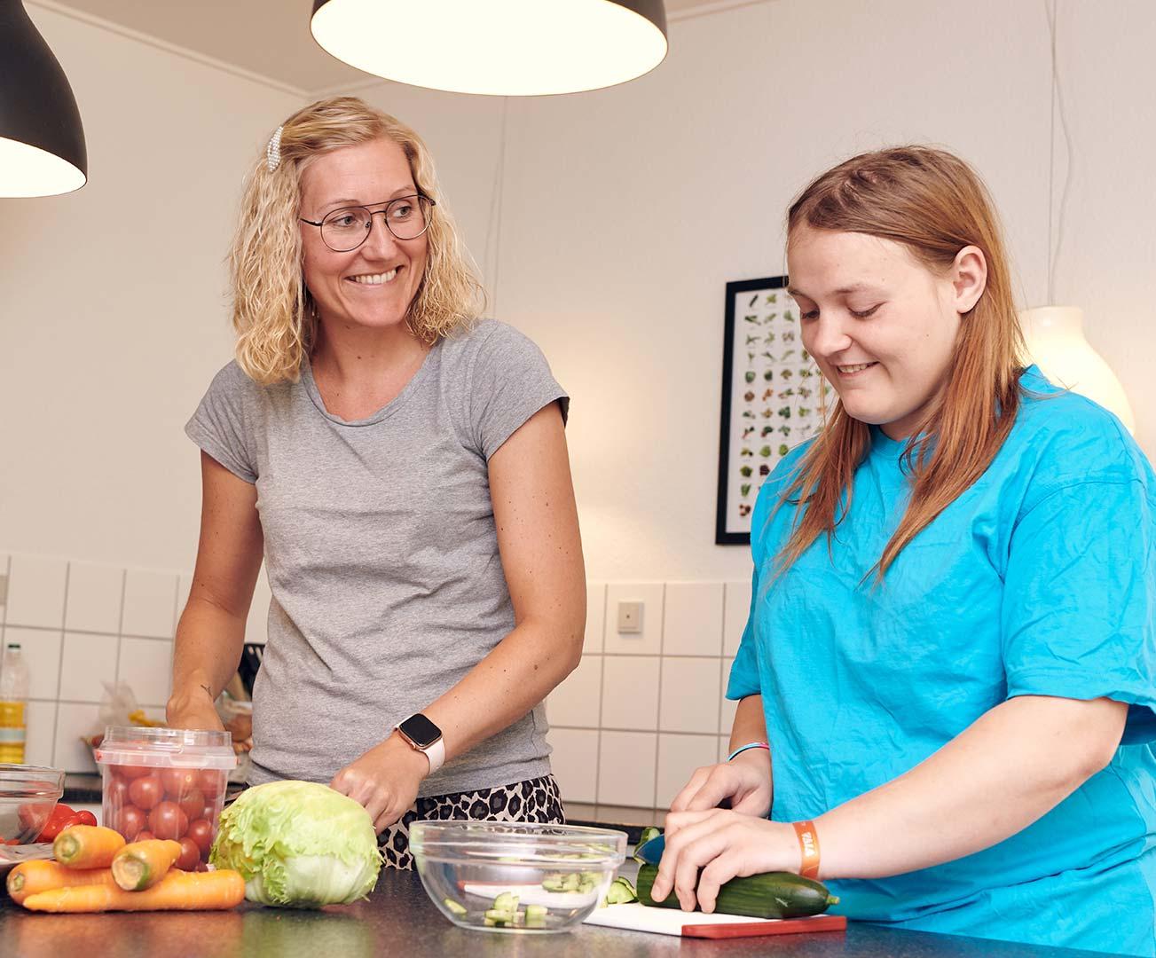 En pædagog og en elev laver mad sammen hos Elmelund