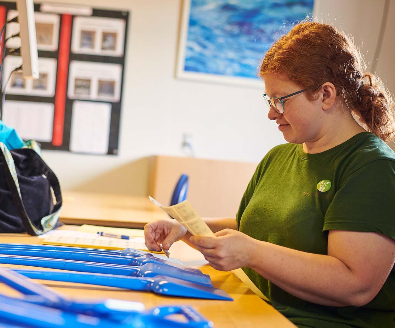 Elev hos Elmelund sætter klistermærker på skovle
